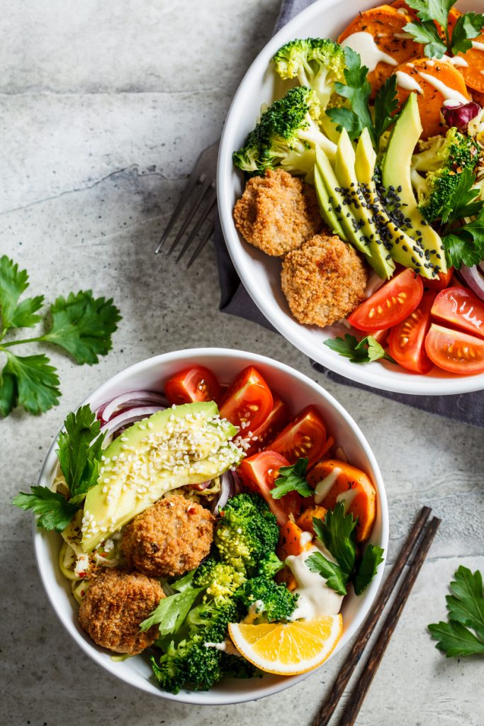 Buddha bowls salad with avocado, sweet potato, falafel, zucchini, tomatoes and broccoli, top view.
