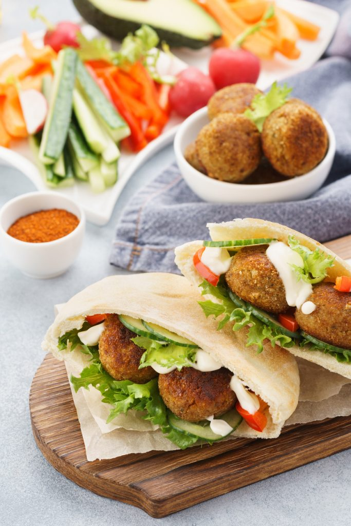 Healthy vegetarian falafel pita with fresh vegetables, lettuce and sauce.