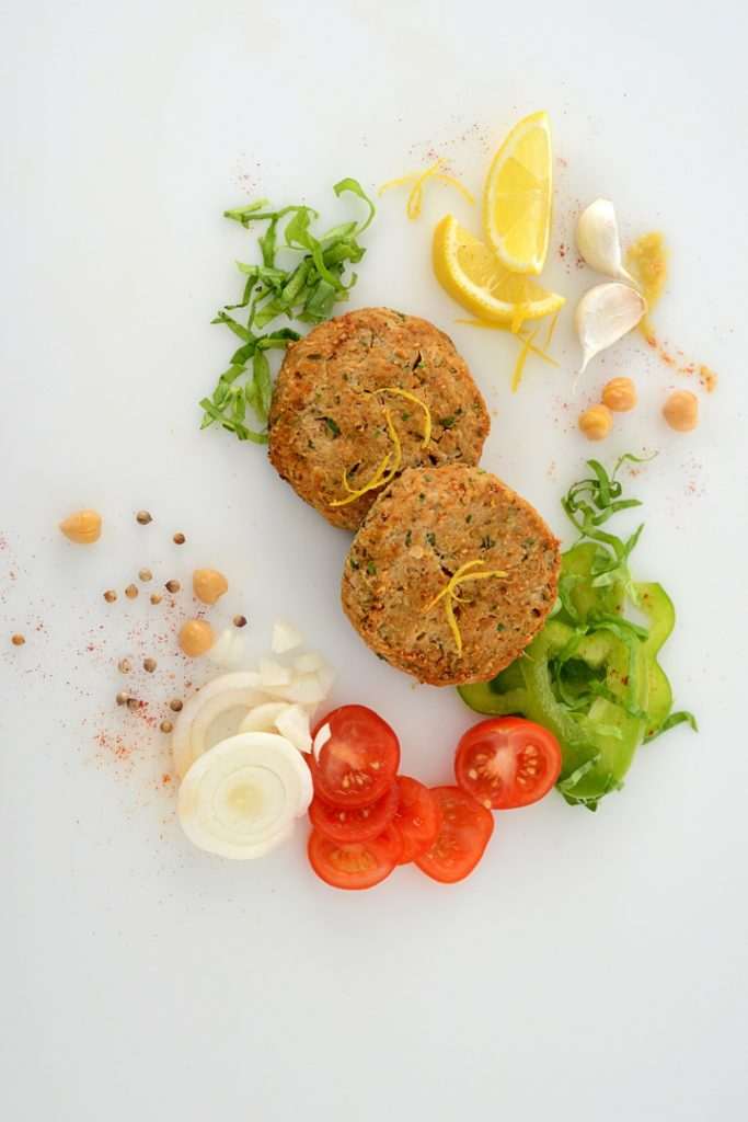 falafel patties on white countertop with lemon, tomato, onions, lettuce, and spices