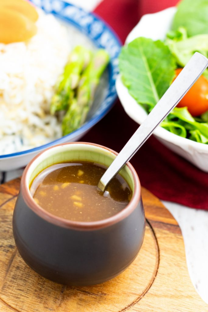 Japanese saucer with miso sauce with salad and rice in background