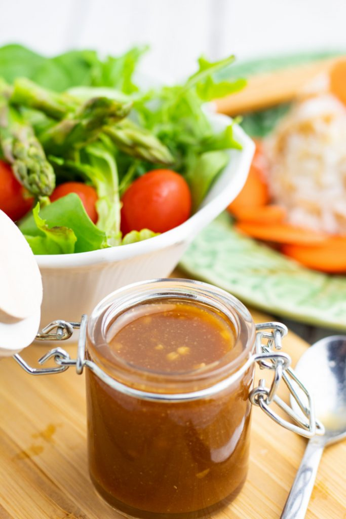 clear container with miso dressing and salad in background