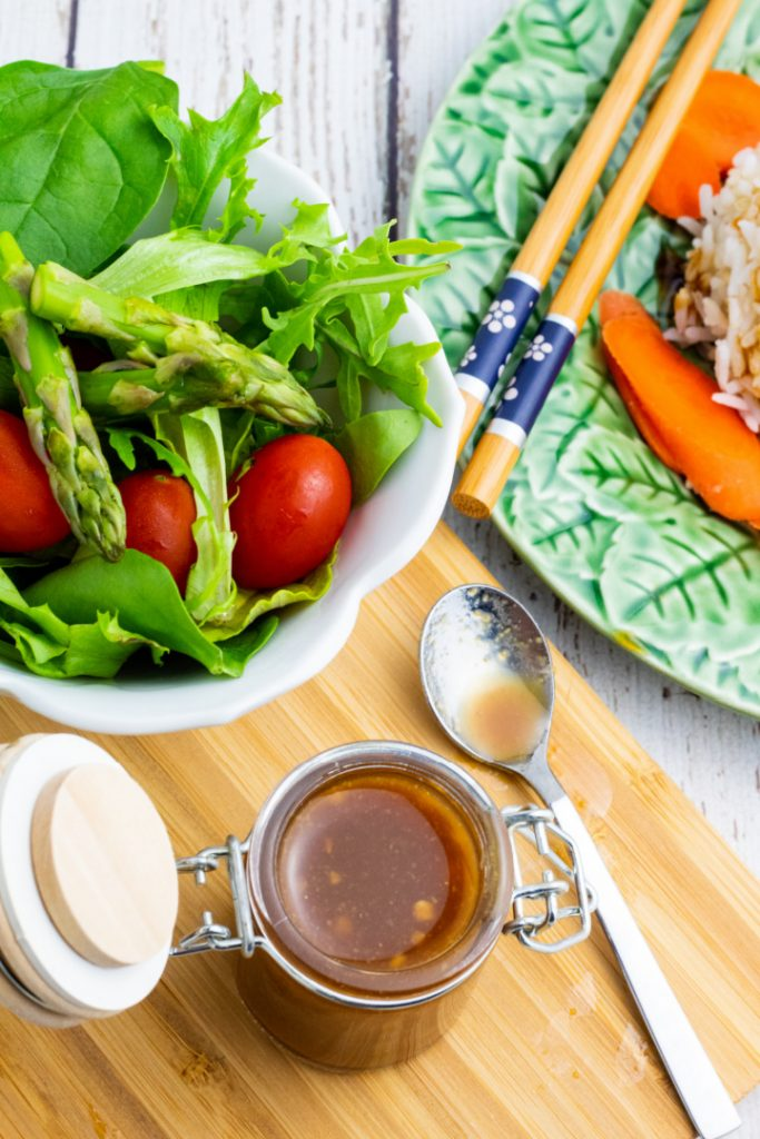 overhead photo of clear dish with miso with bowl of salad