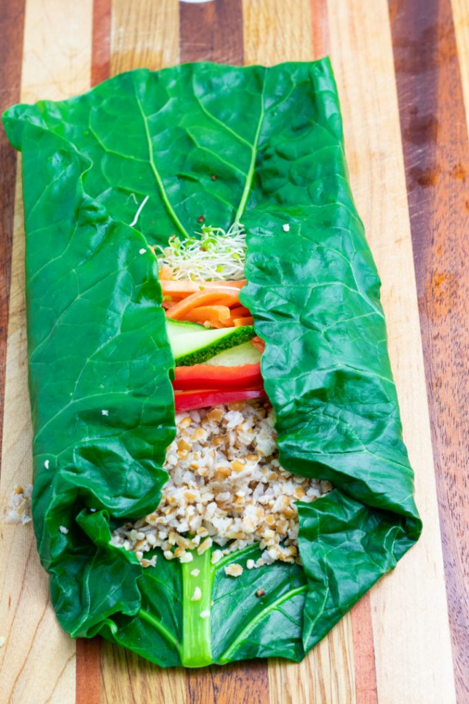 blanched collard leaf on wooden cutting board filled with veggies and sides folded in