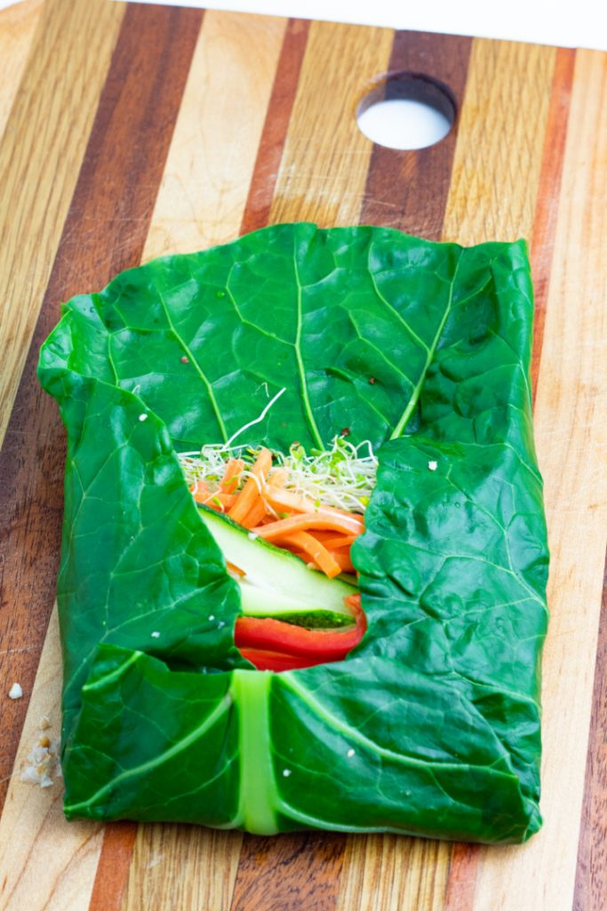 blanched collard leaf on wooden cutting board filled with veggies and sides folded in and bottom folded up