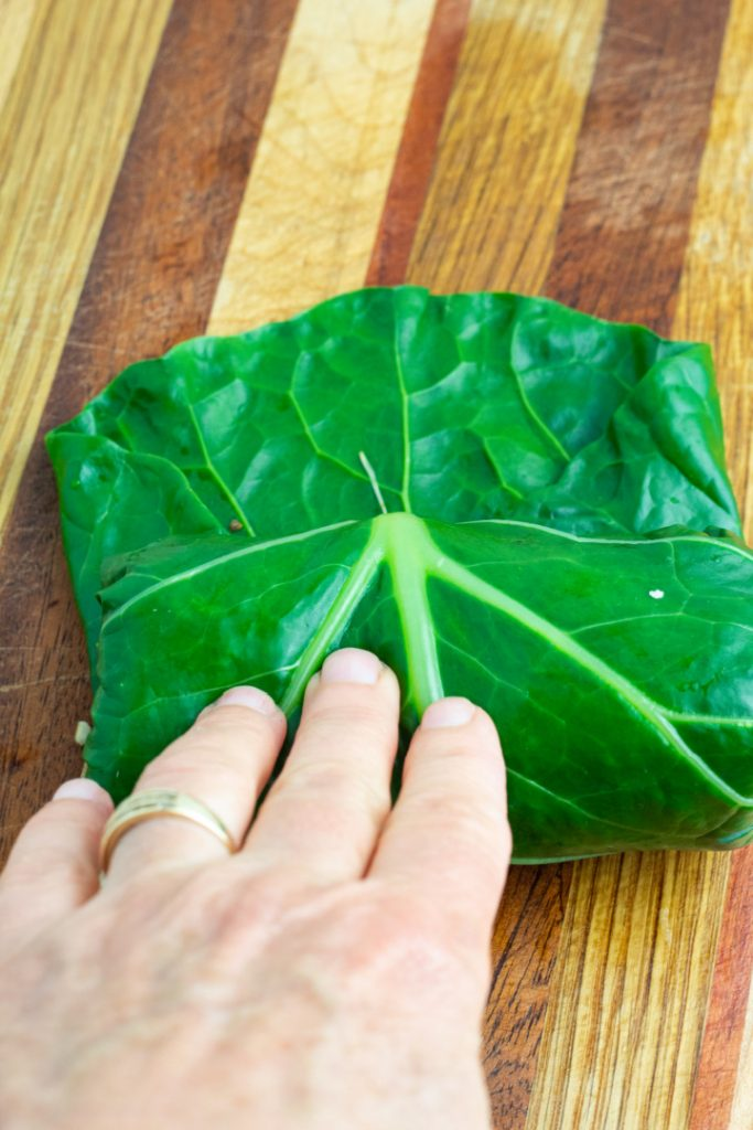 stuffed collard leaf being rolled up with hands