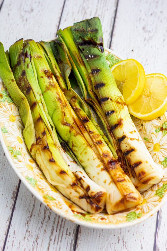 grilled leeks with lemon slices on daisy oval plate