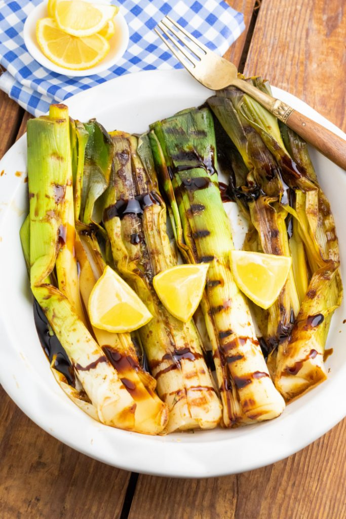 grilled leeks with lemon slices on white plate