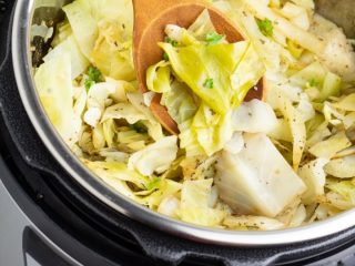 instant pot full of cooked cabbage with a wooden spoon
