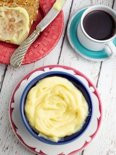 bright colorful bowl and saucer filled with plant based butter, toast and coffee in background