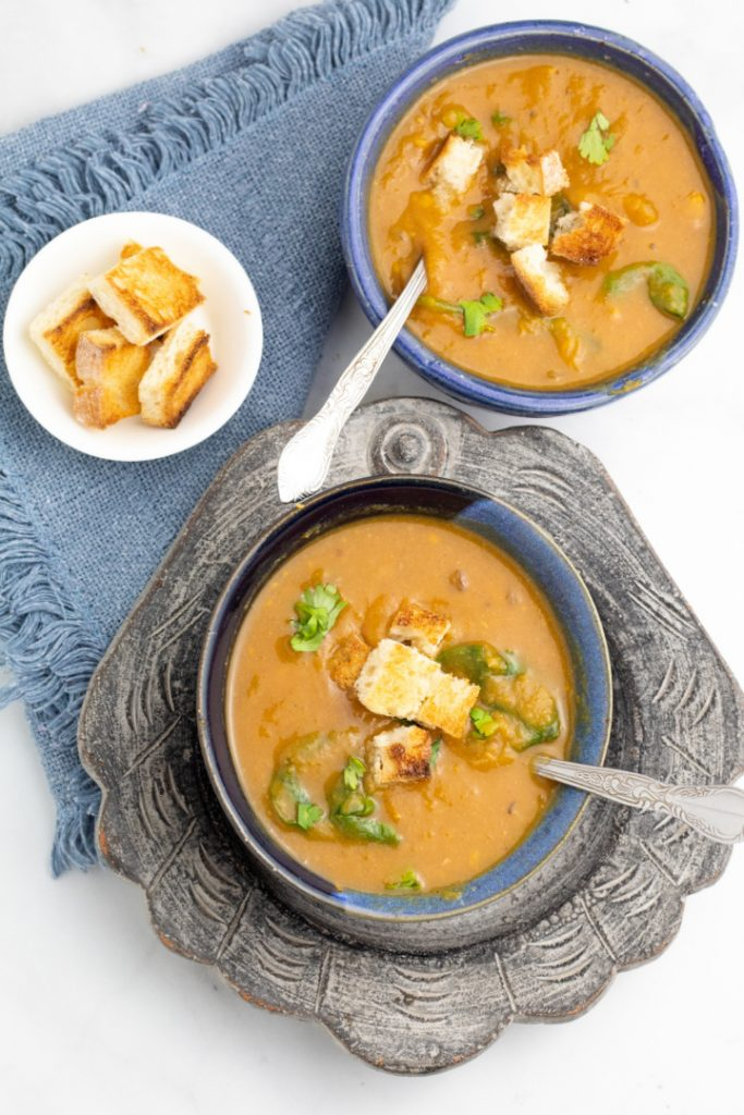 two blue bowls filled with vegan sweet potato soup topped with croutons