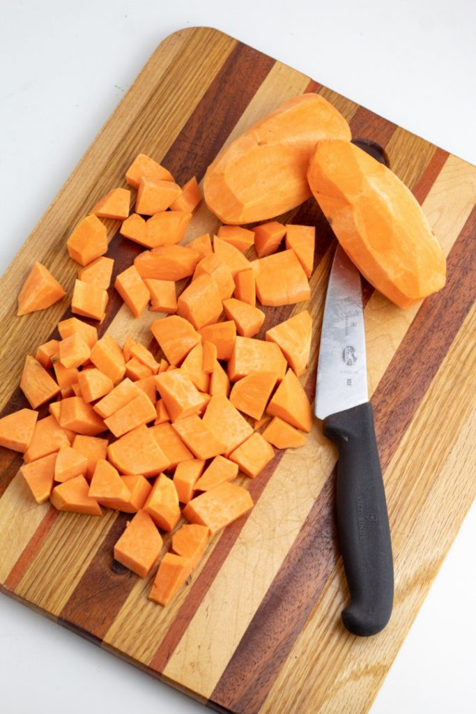 sweet potatoes being diced on wood cutting board