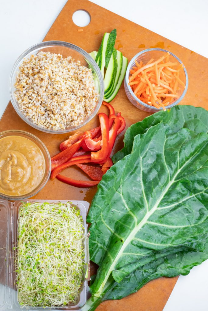 whole collard leaf, bean sprouts, bulgur, grated carrots, red bell pepper slices, cucumber slices, peanut sauce on cutting board