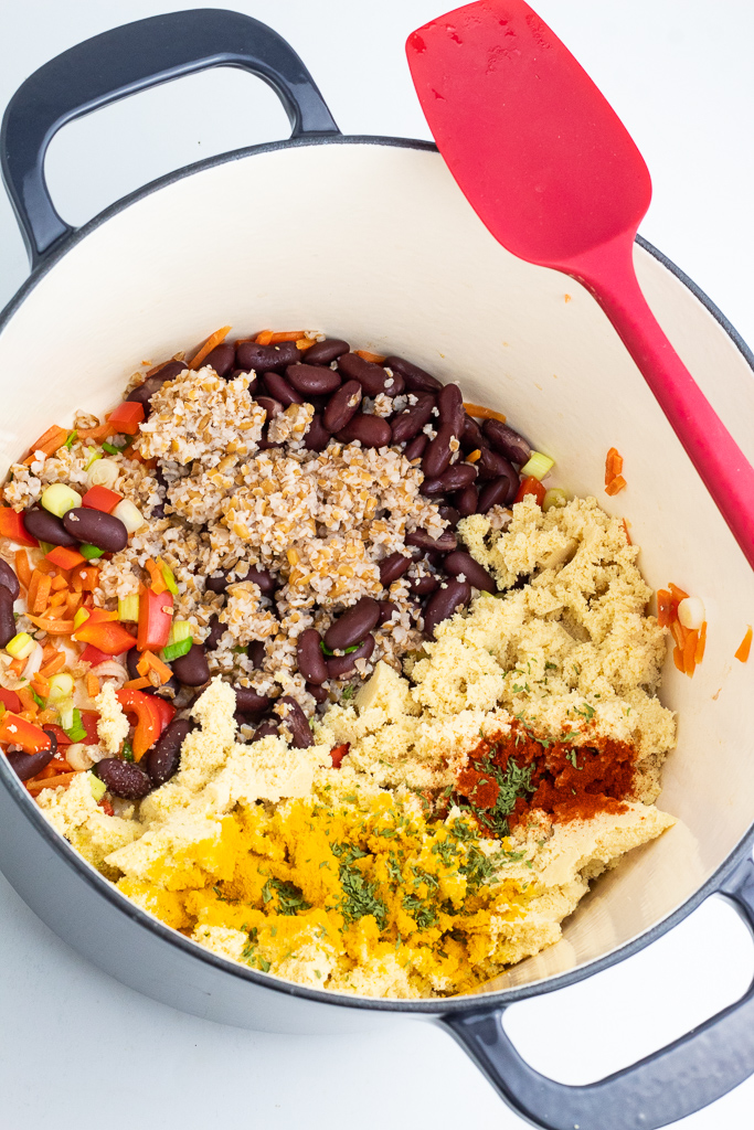 pot with blue handles filled with beans, tofu, bulgur, vegetables