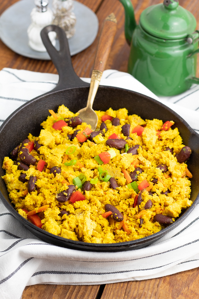 black cast iron skillet filled with breakfast hash on a wooden table