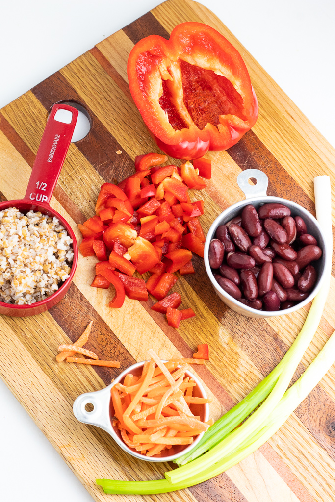 kidney beans, grated carrots, red bell pepper, and green onions on wood cutting board
