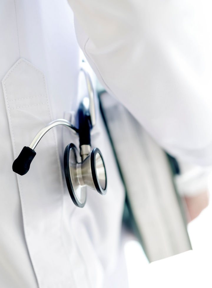 Closeup stethoscope in coats pocket, doctor holding book with stethoscope in coats pocket on white background.
