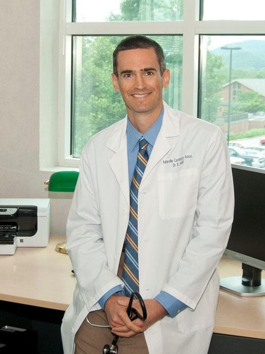 cardiologist in lab coat leaning against desk