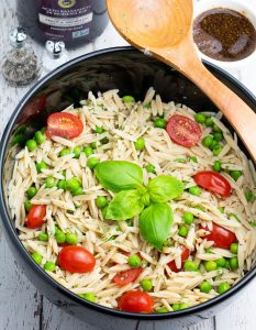 orzo pasta with tomatoes, green peas, and basil in large black bowl with wooden spoon