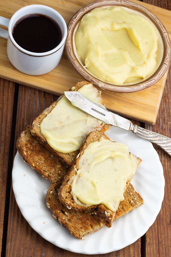 overhead photo of 4 slices of toast topped with plant based butter on wooden table