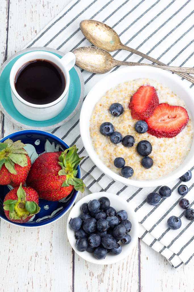 overhead shot of bowl of steel cut oatmeal topped with berries, bowl of strawberries and coffee