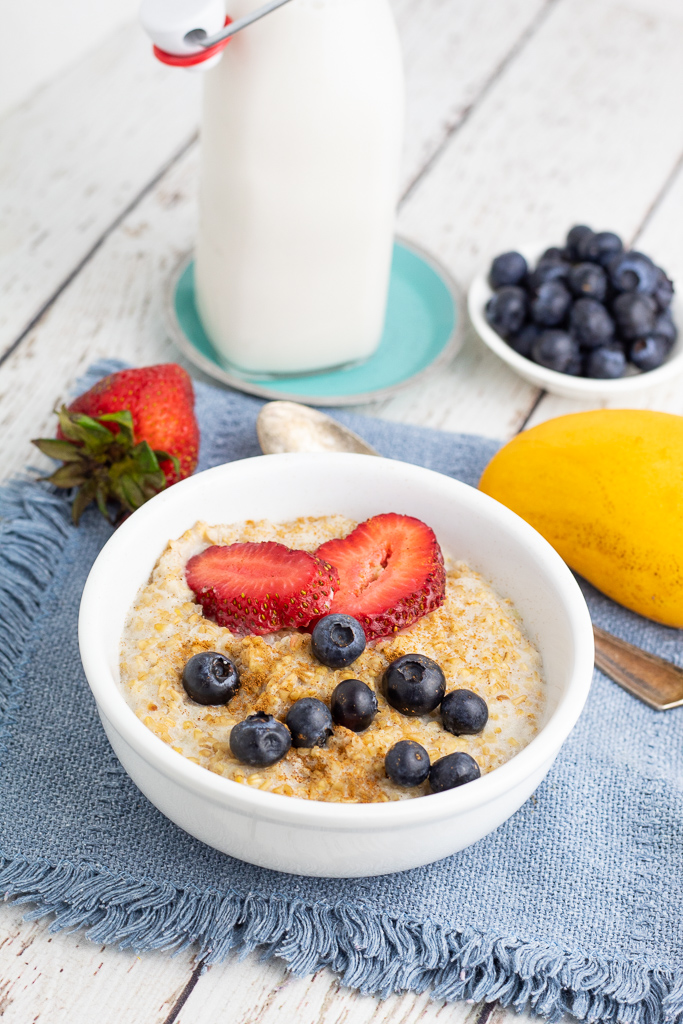 white bowl of of steel cut oats with jar of almond milk and berries in background