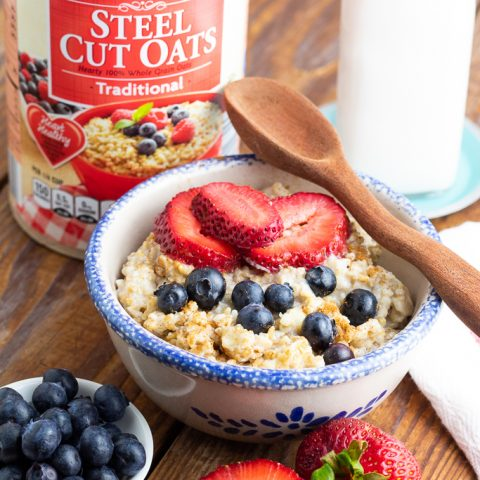 blue rimmed bowl filled with cookd steel cut oatmeal with wooden spoon on table with box of steel cut oats