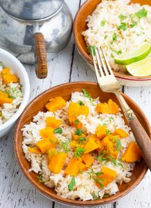 two wooden bowls of sweet potatoes and rice with sauce