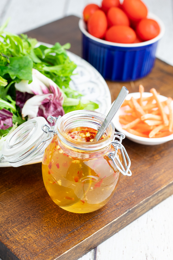 glass jar of oil free salad dressing with spoon beside salad and vegetables