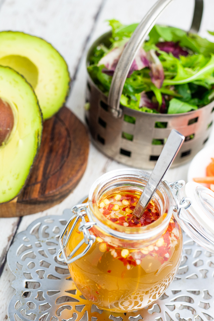 round glass jar with lid filled with oil free vinegar sauce in front of basket of salad