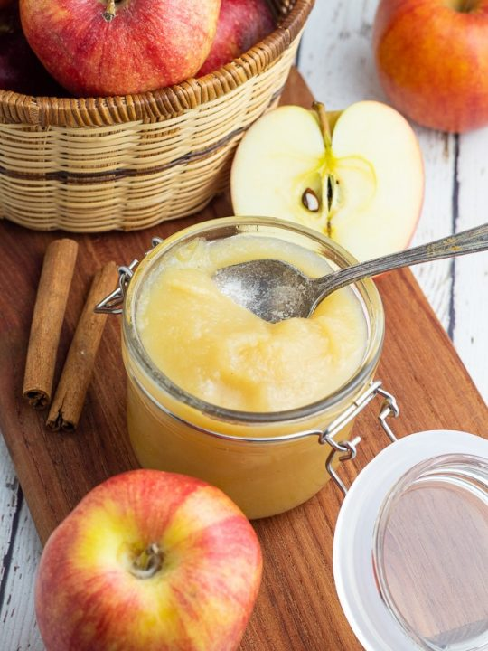 homemade unsweetened applesauce in jar with lid surrounded by red apples