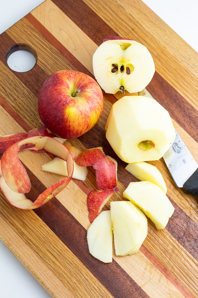 apple being peeled on wooden cutting board with other apples