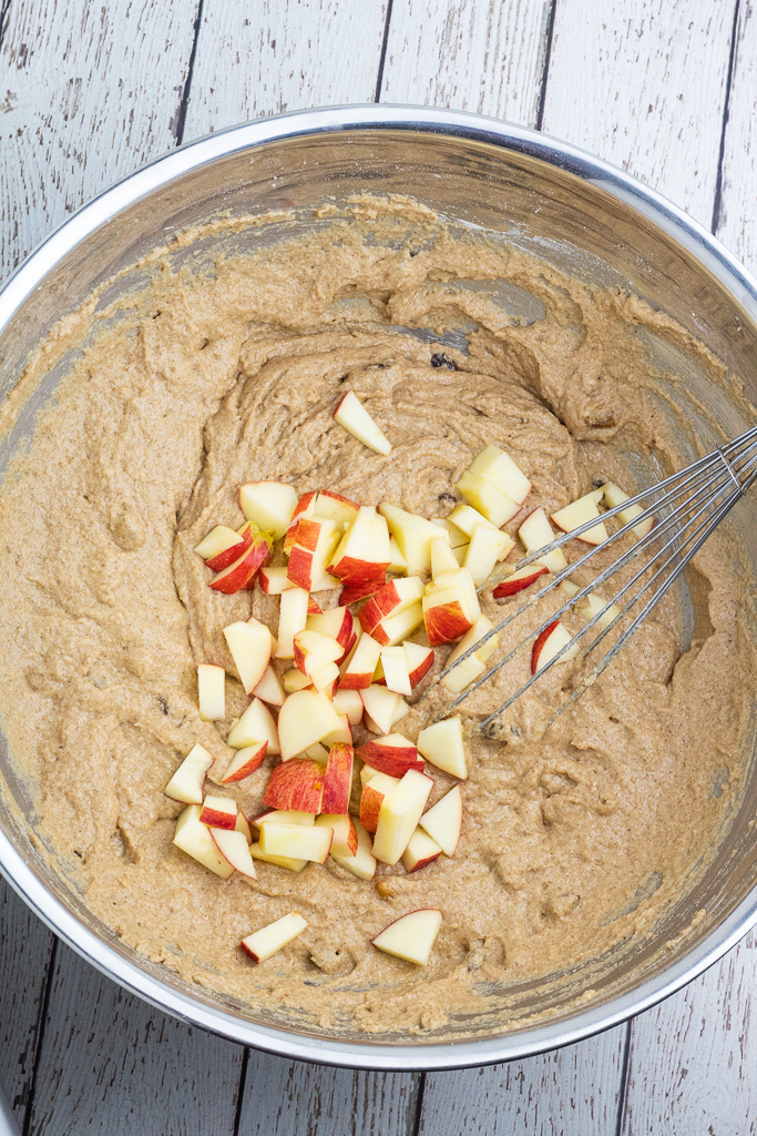 large stainless mixing bowl with applesauce muffin batter topped with diced apples