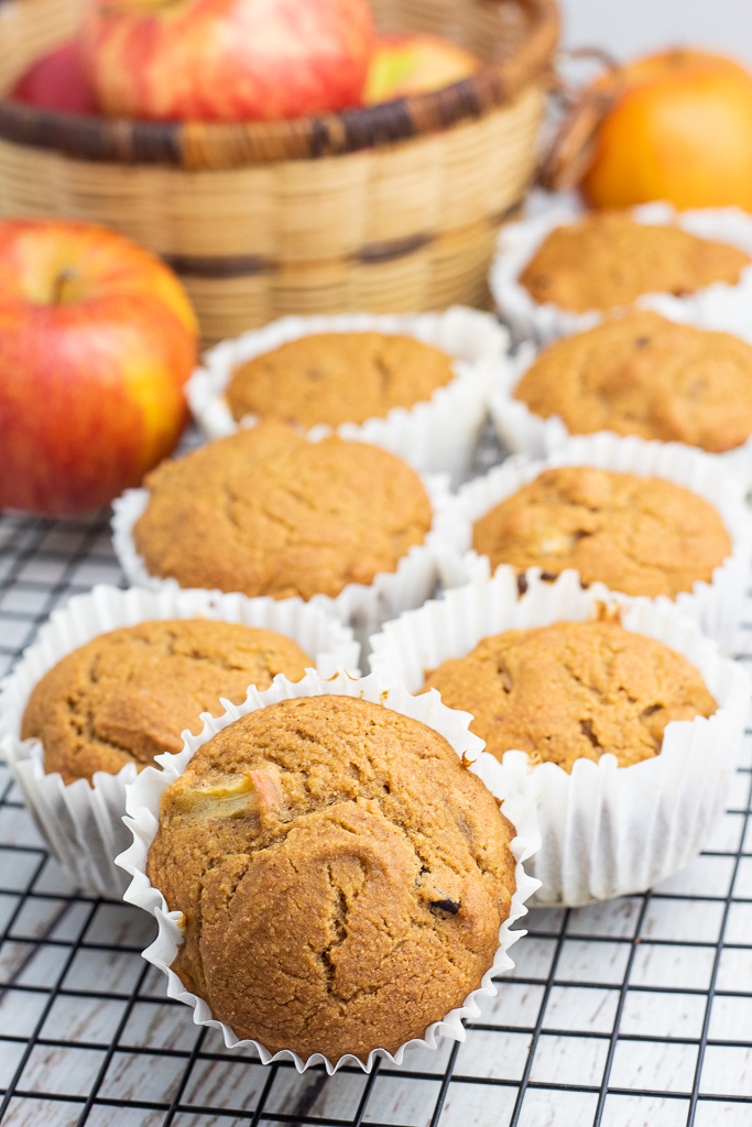 line of vegan muffins in white paper cups on cooling rack with apples in background
