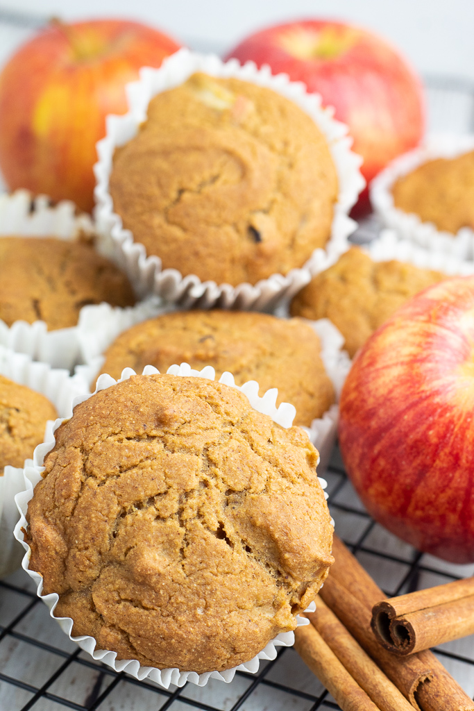 close up of vegan muffins in white paper cups with apples and cinnamon sticks