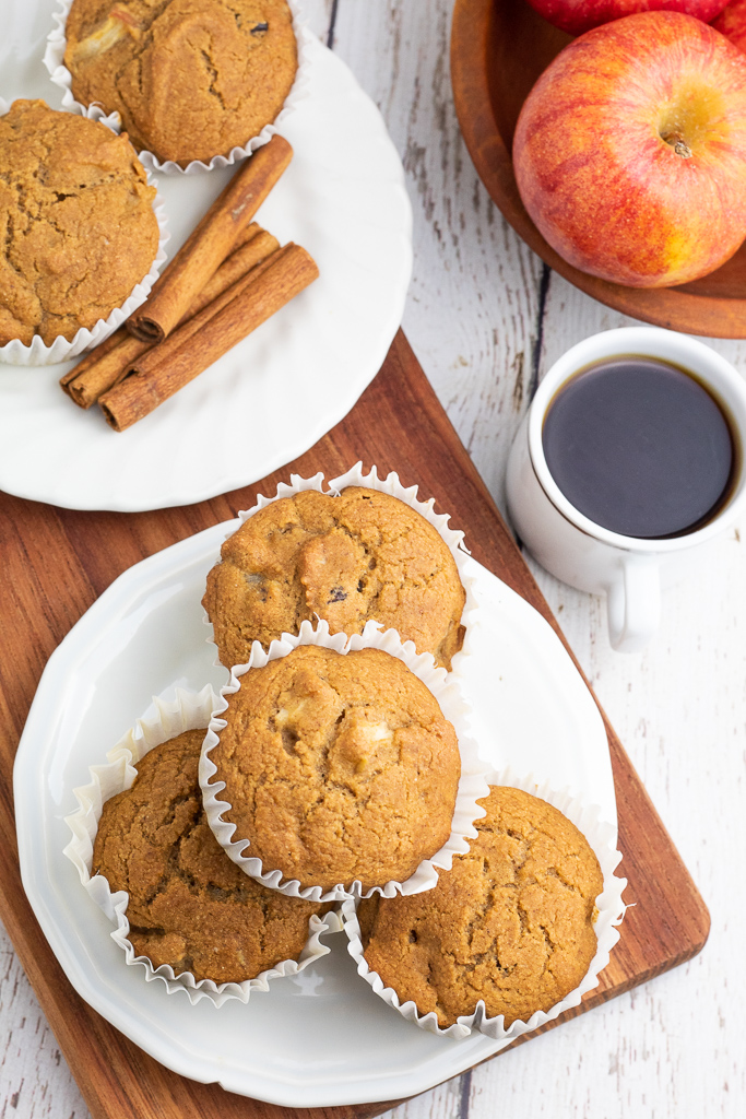 overhead photo of plate of muffins stacked on white plate with cup of coffee