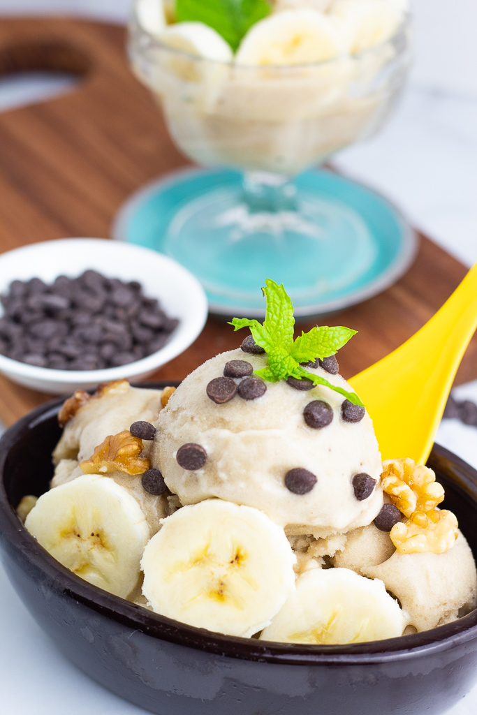 black dish full of vanilla nice cream topped with vegan chocolate chips and mint leaf