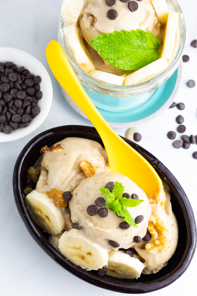 overhead shot of black oval dish of vanilla nice cream topped with chocolat chips and bright yellow spoon