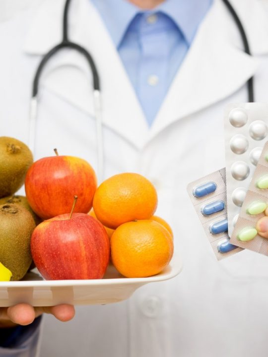 doctor holding tray of fruit and pills