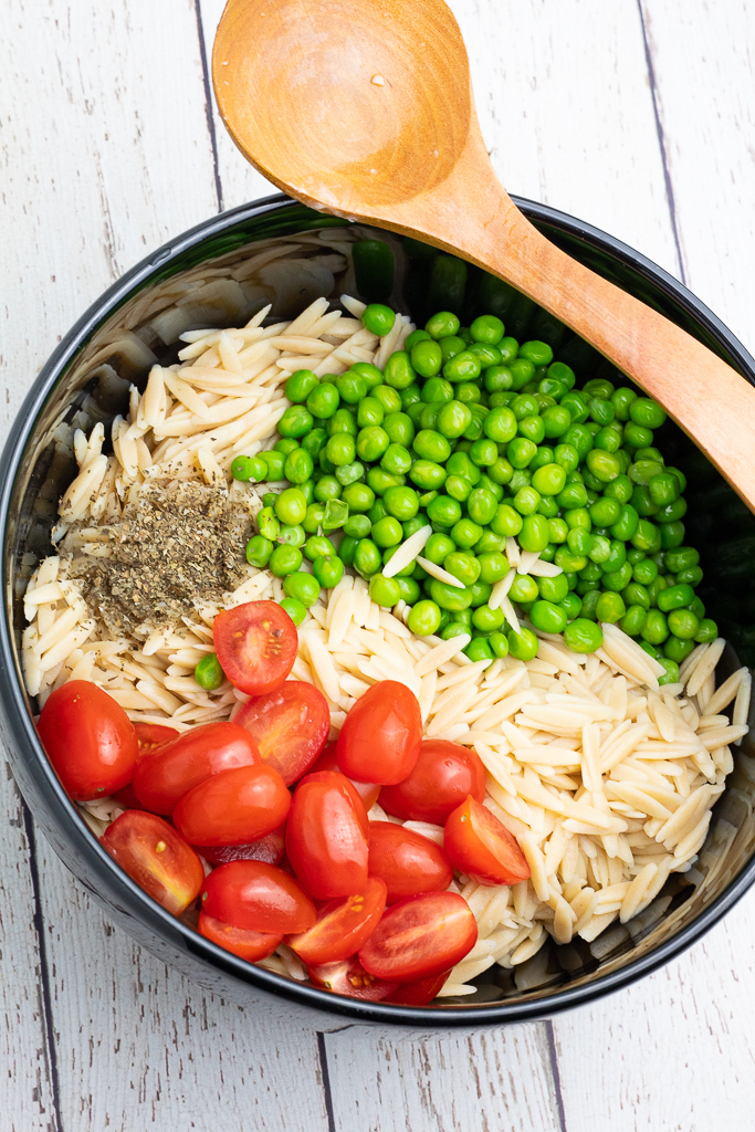 large black bowl with cooked orzo pasta, tomatoes, green peas, and spices