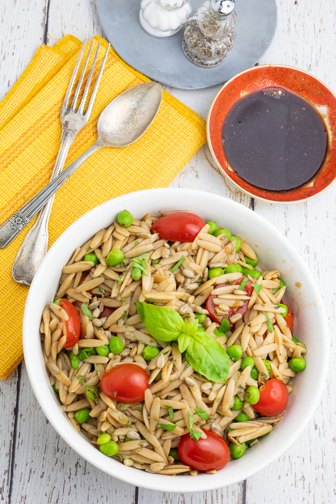 overhead photo of orzo pasta with tomatoes, green peas, and basil in white bowl with balsamic vinegar sauce