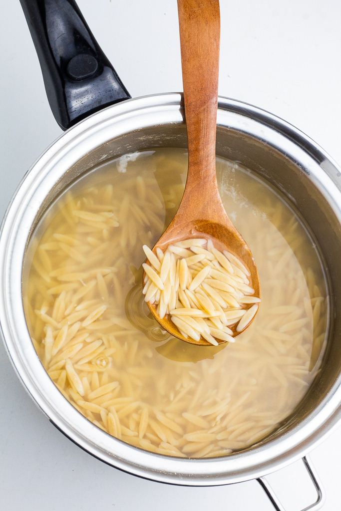 saucepan with cooked orzo pasta in water and a wooden spoon