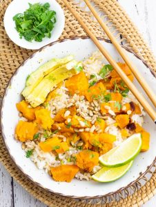 white bowl filled with rice, sweet potatoes, sesame seeds, cilantro, and sauce with chopsticks