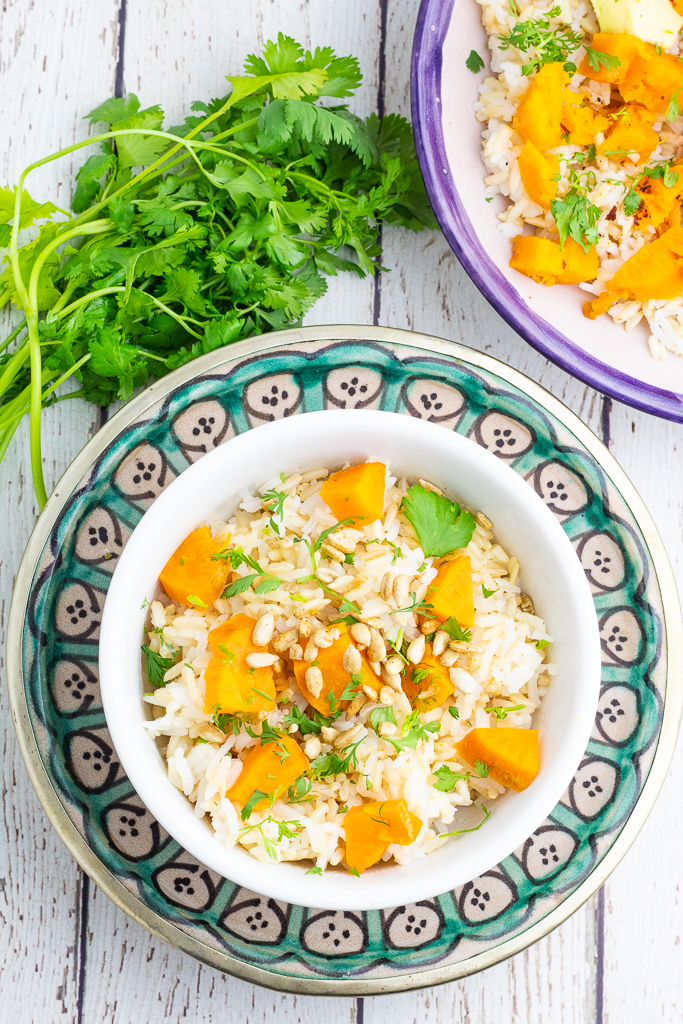 colorful bright plate with white bowl of rice and sweet potatoes with bunch of cilantro