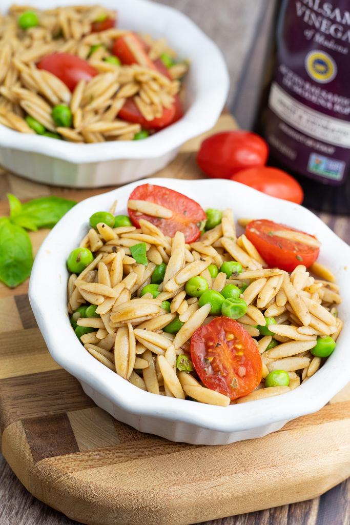two white bowls with orzo vegan pasta salad