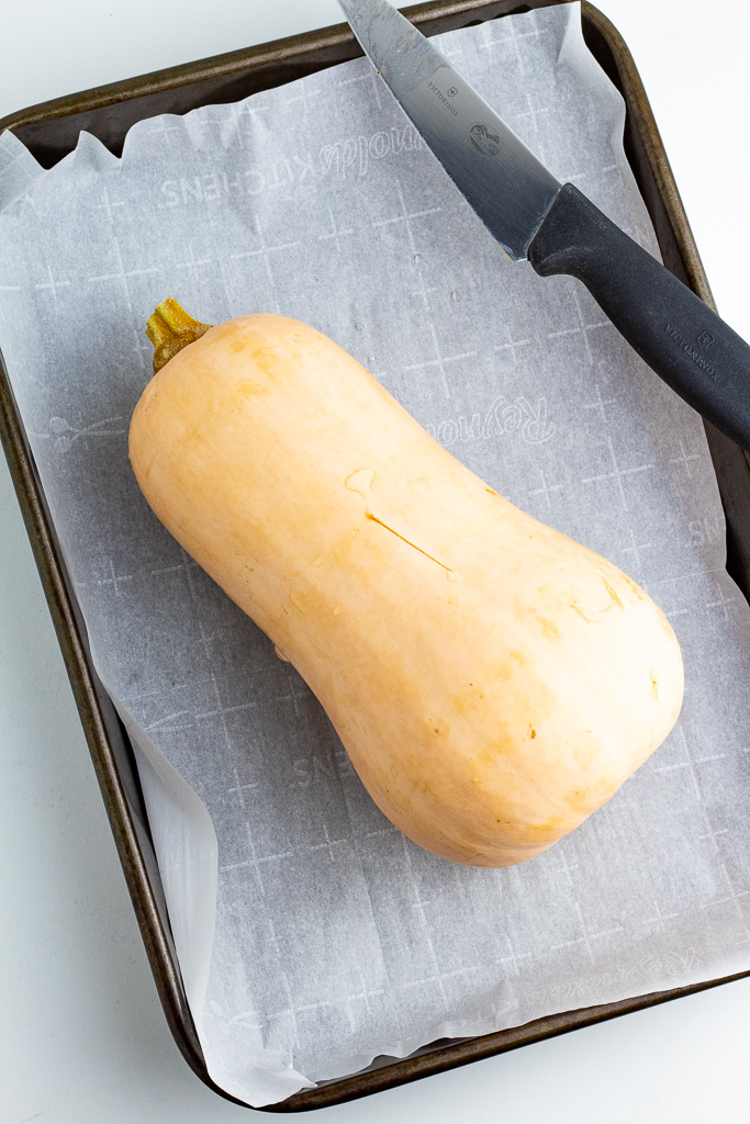 baking pan lined with parchment paper with a whole butternut squash