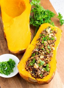 2 halves of a baked butternut squash one is stuffed with rice and one plain