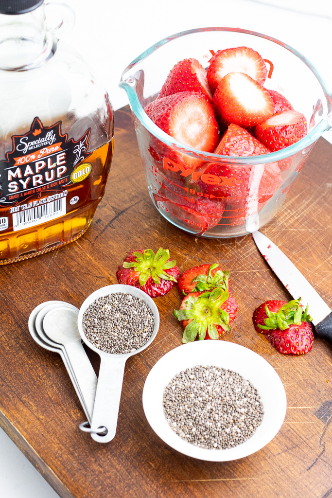 measuring cup full of chopped strawberries, bottle of maple syrup, and measuring spoon with chia seeds