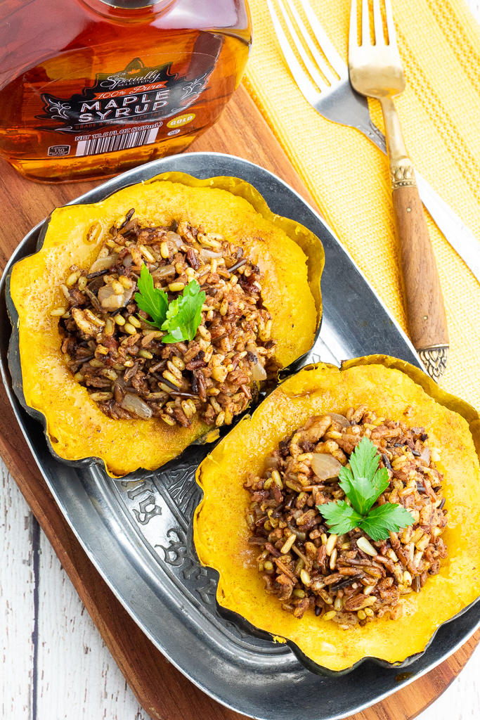 overhead shot of 2 stuffed acorn squash in silver pan with forks and maple syrup