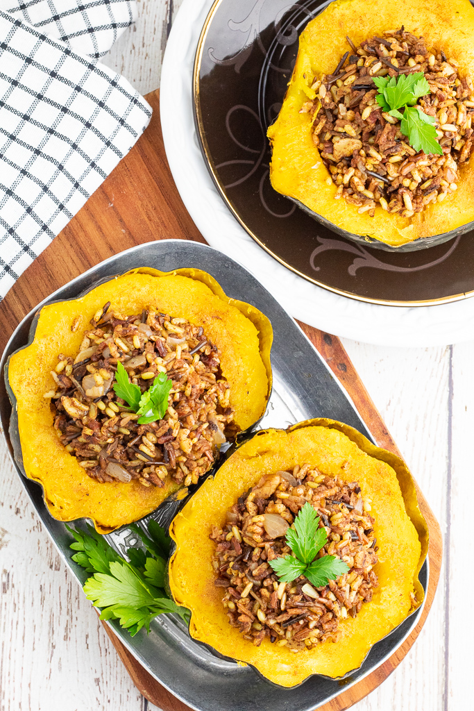2 acorn squash stuffed with wild rice and seasonings in silver dish