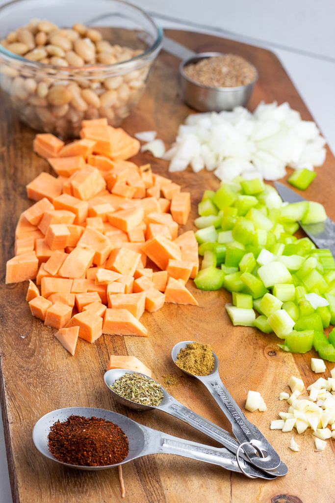 diced sweet potatoes, onions, celery, beans, and spices on cutting board